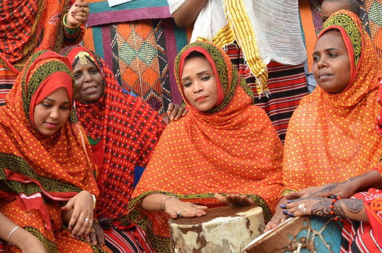 Eritrean women sing using Sudanese daloka (drum)