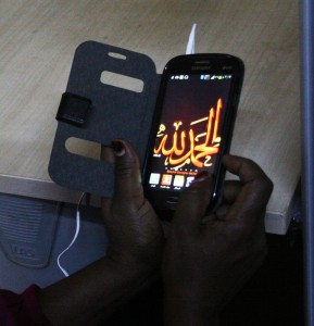 """A woman wrote on her cell phone """"Praise be to Allah"""""""
